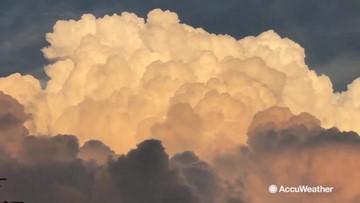 Beautiful billowing clouds turn bright orange at sunset
