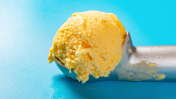 spoon with mango flavor ice cream ball on blue background close up