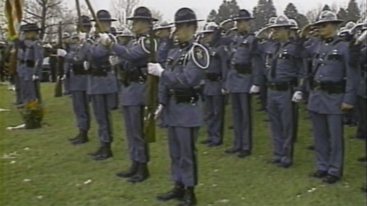 Fellow Maine State Troopers stood in the rain to pay their respects at the burial of Det. Giles Landry at Gracelawn Memorial Park in Auburn in April 1989