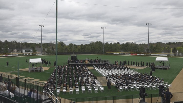 Husson University graduates 'fly' across the stage Saturday.