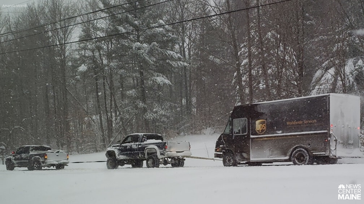 Trucks pull UPS truck out of snow