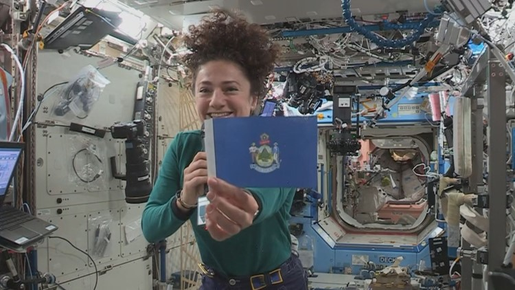 Jessica Meir in space flying a Maine flag
