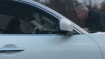 A 65-year-old man rides on the hood of a car on the highway in a road rage incident