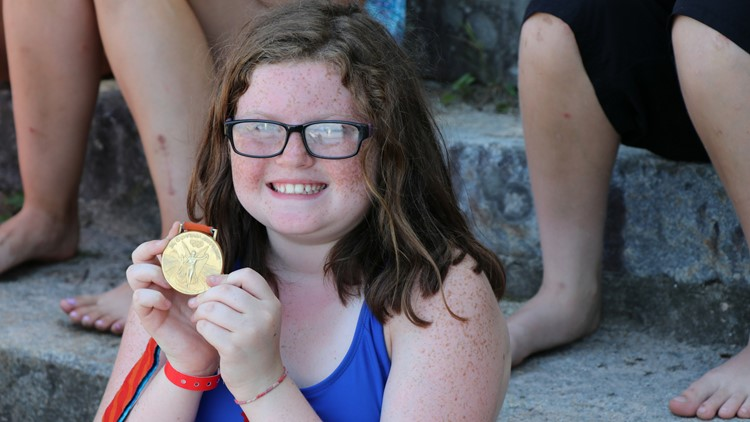 The chance to hold Ian Crocker's Olympic medals brought smiles to the faces of kids at Camp Sebago in Standish
