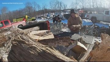 Volunteers split logs to help people stay warm this winter