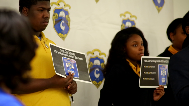 National Collegiate Prep students hold signs