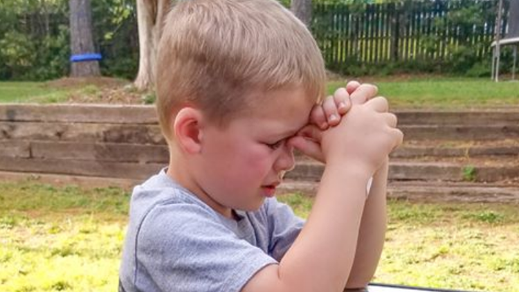 4-year-old Owen Hanes prays for his grandfather